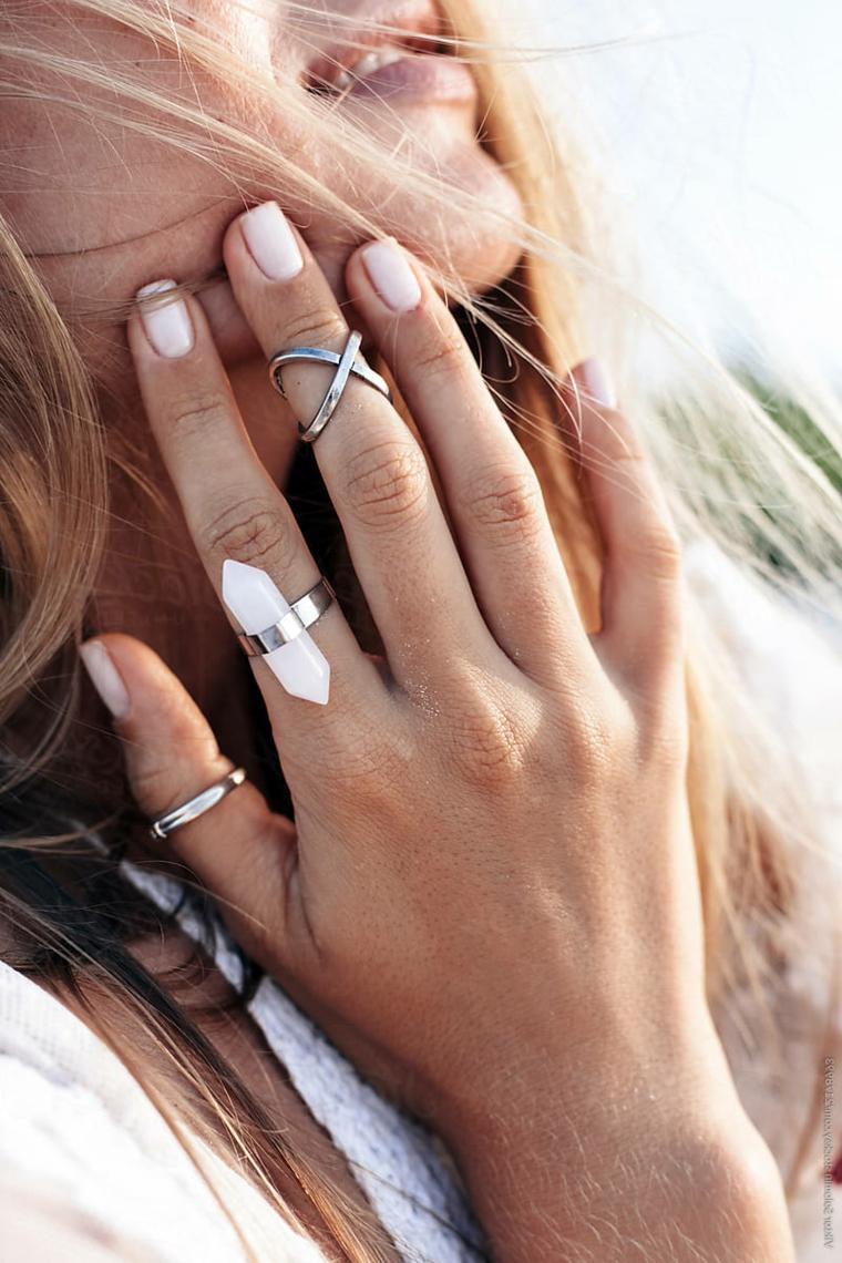 Unghie estive, smalto di colore bianco, anelli di argento, donna con capelli biondi
