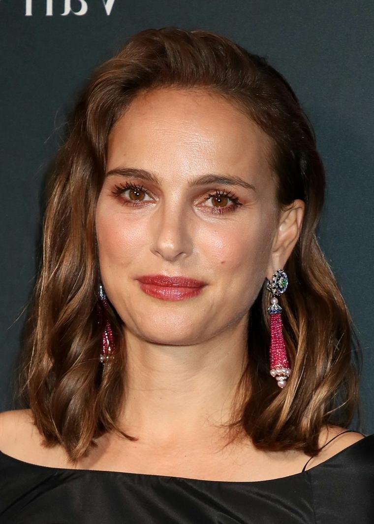 L'attrice Natalie Portman, capelli mossi castani, orecchini pendenti, capelli scalati