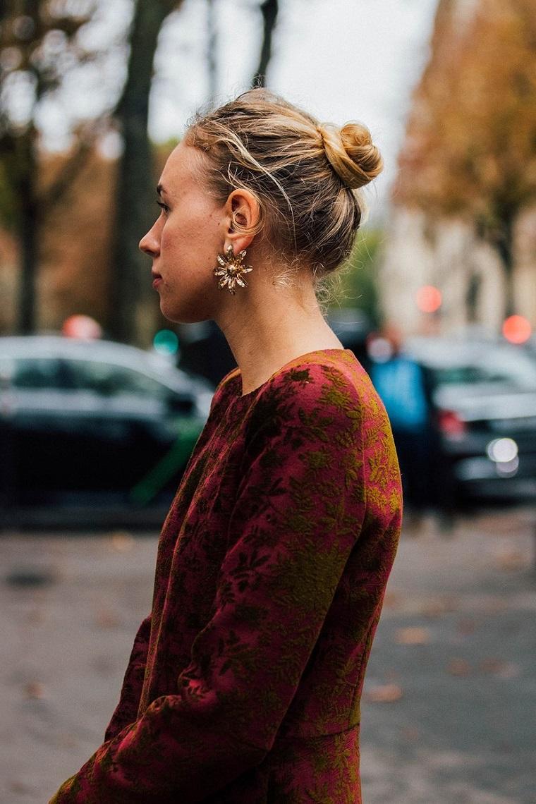 Acconciature morbide, donna con capelli biondi, orecchini pendenti, chignon alto mosso