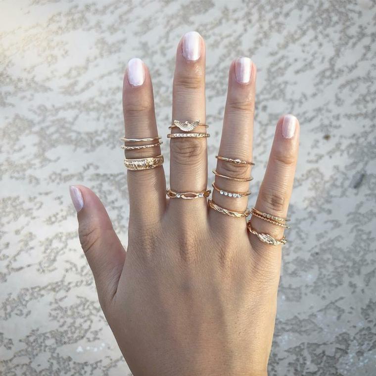 Smalto per unghie colore argento, anelli in oro, unghie forma arrotondata, colate estive