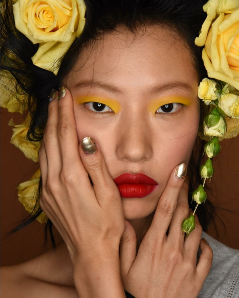 Donna con fiori in testa, smalto color argento lucido, unghie gel semplici, ombretto giallo