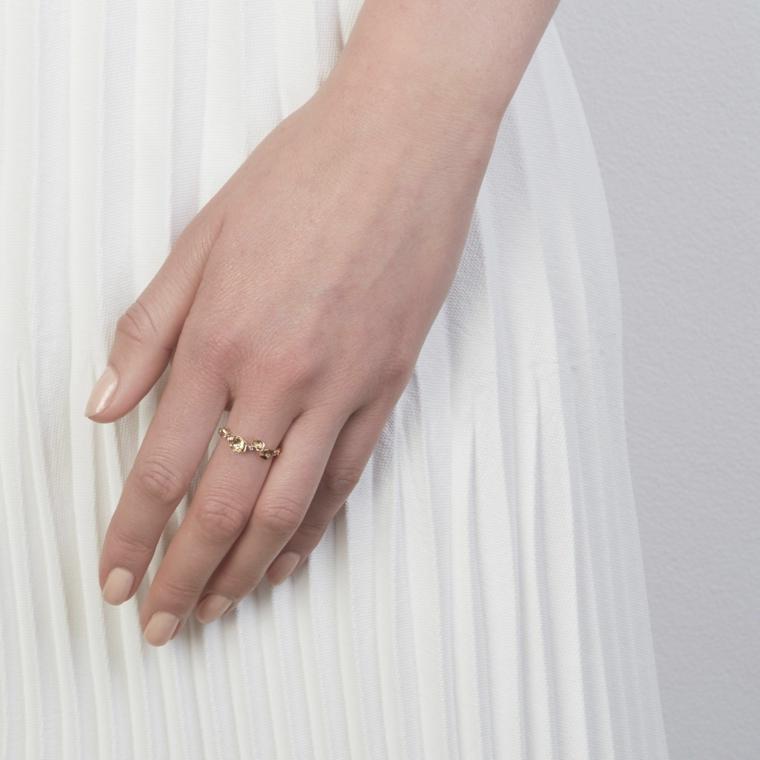 Unghie gel semplici, smalto di colore beige, manicure forma arrotondata, anello sul dito medio