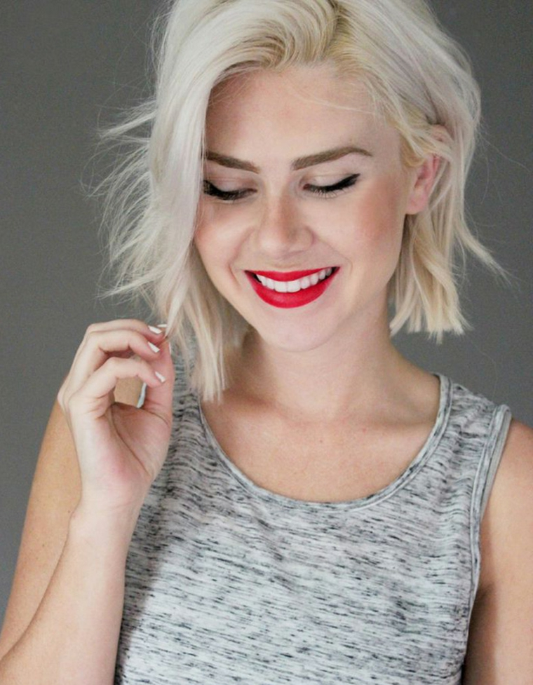 Ragazza con rossetto rosso, capelli biondo ghiaccio, taglio caschetto corto