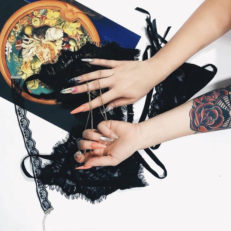 Donna con manicure stiletto, tattoo vecchia scuola, disegno old school rosa