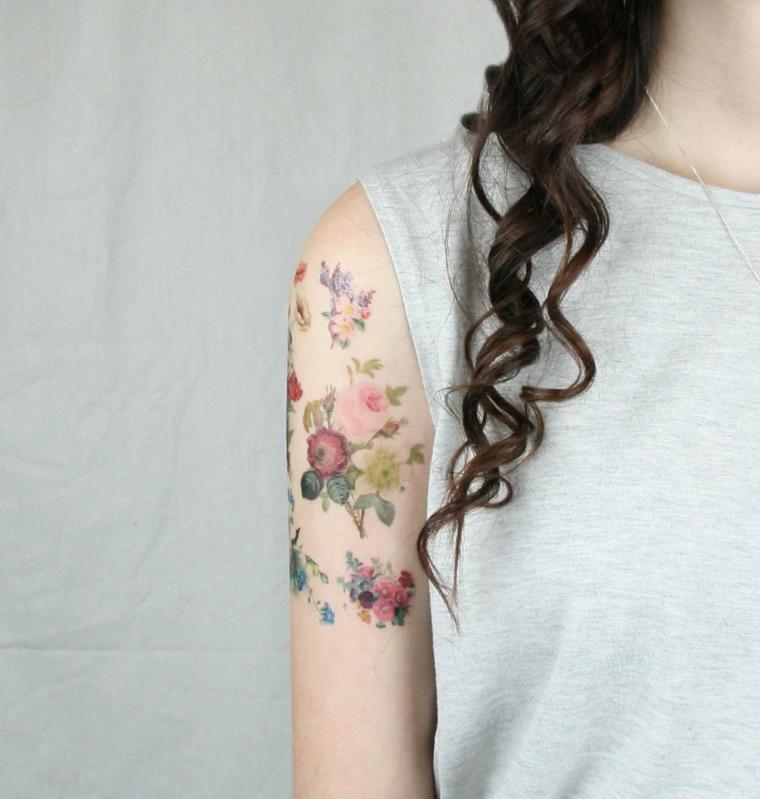 Donna con capelli ricci, spalla donna tatuata, cuore sacro tattoo, top senza maniche grigio