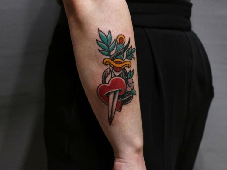 Disegno tattoo colorato, coltello che affligge un cuore, tatuaggio sull'avambraccio