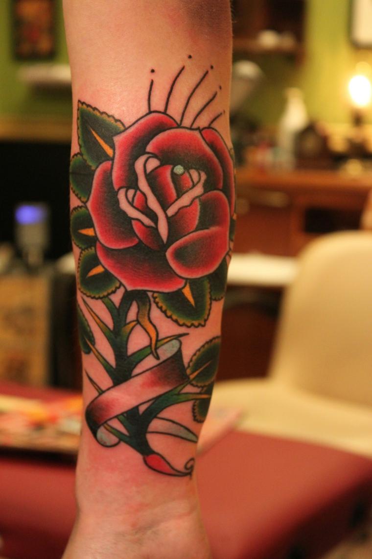 Tattoo old school braccio, disegno rosa rossa, tatuaggio sull'avambraccio, la mano di una donna