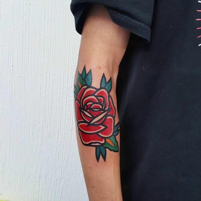 Uomo con avambraccio tatuato, disegno tattoo fiore rosso, tatuaggio cuore significato
