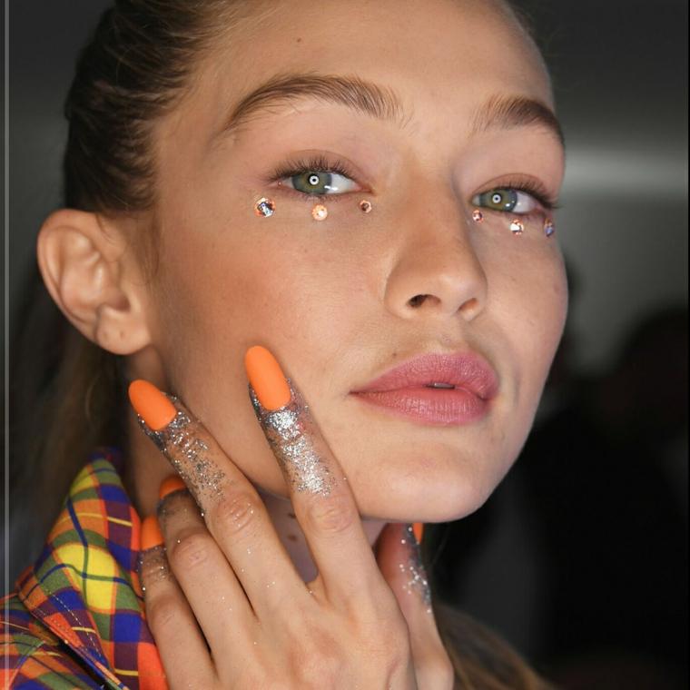 Immagini di unghie con gel, unghie colore arancione, brillantini incollati sotto gli occhi