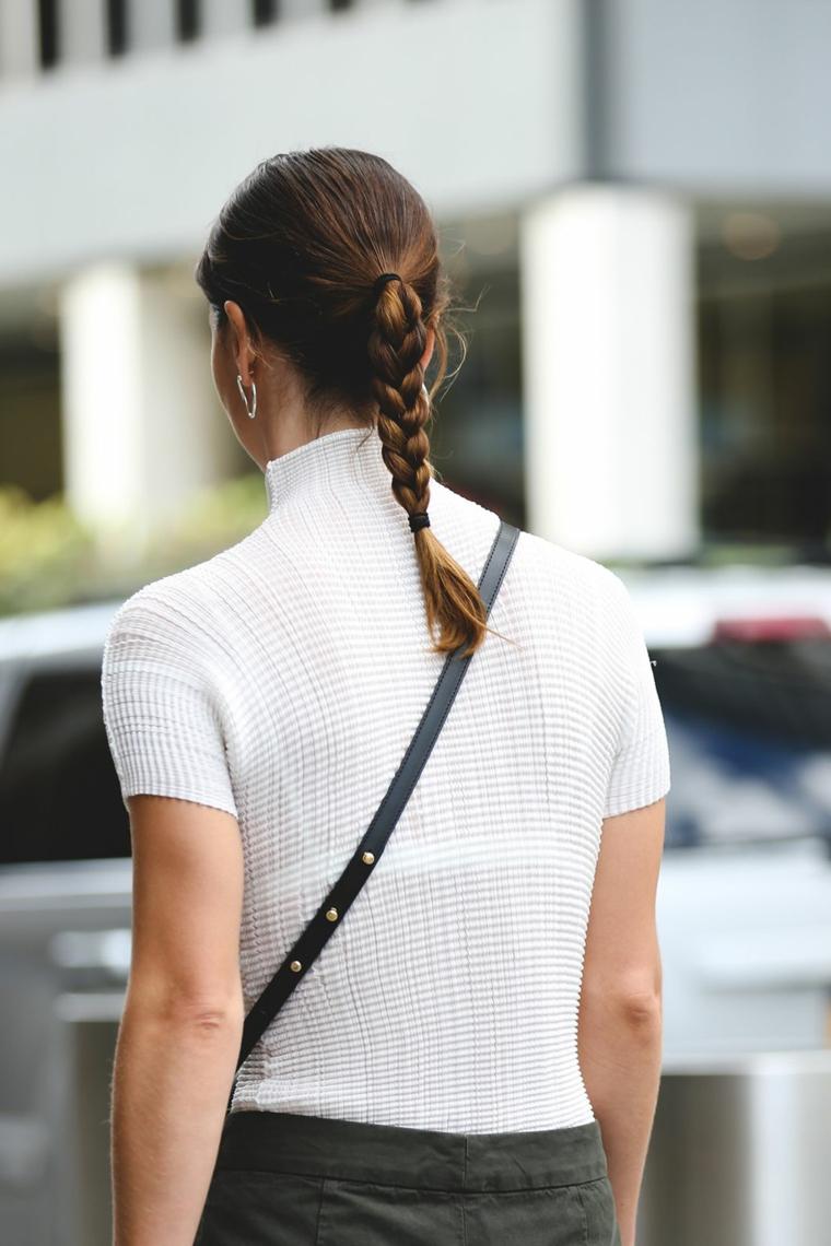 Acconciatura con treccia laterale, capelli colore castano, coda con treccia, donna girata di spalle