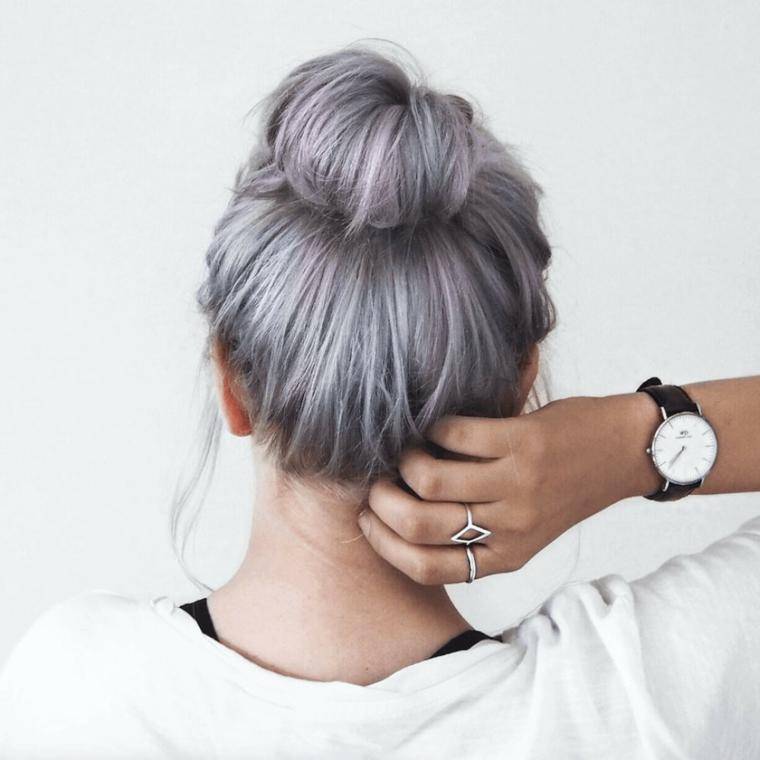 Pettinatura con chignon mosso, shatush grigio, mano con anelli in argento, donna girata di spalle