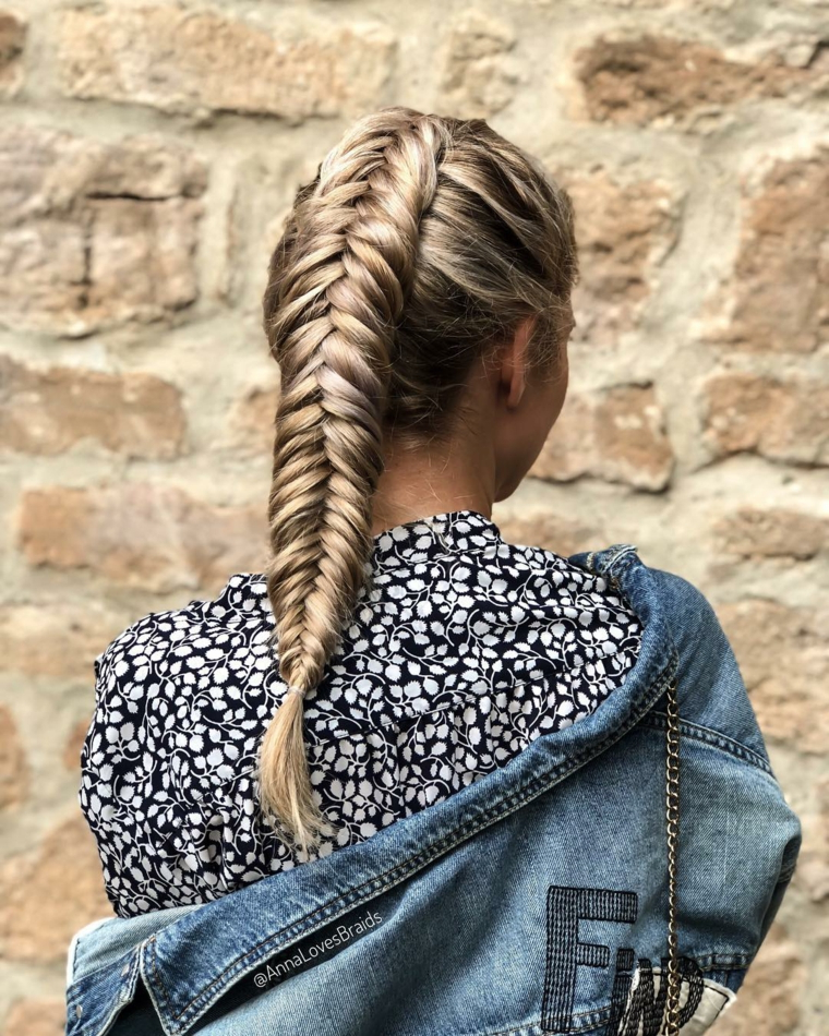 Donna con capelli biondi, treccia a spina di pesce, giacca in jeans con scritte