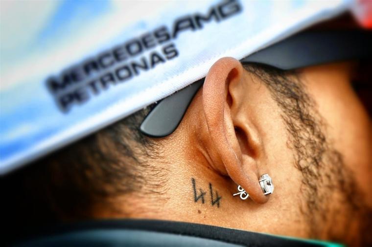 Tatuaggio dietro l'orecchio, uomo con orecchino, tattoo stilizzati