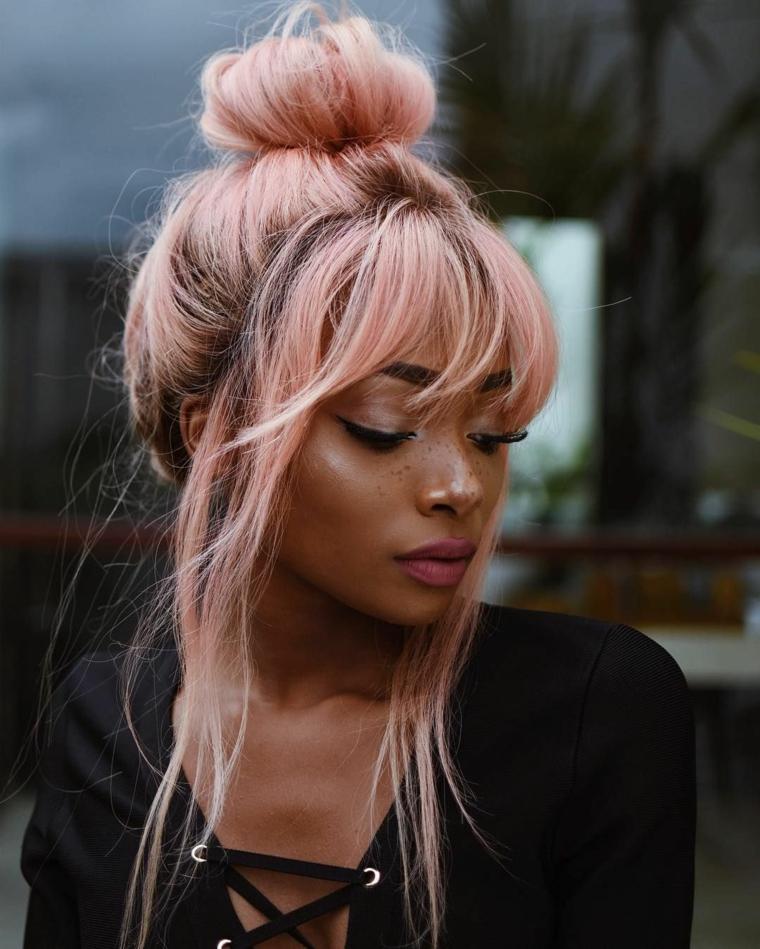 Tinta capelli rosa pastello, acconciatura con chignon, pettinatura con frangia