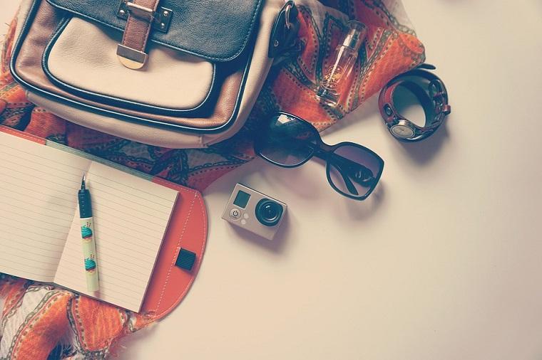 Come organizzare un viaggio low cost, borsa con tracolla, quaderno con penna