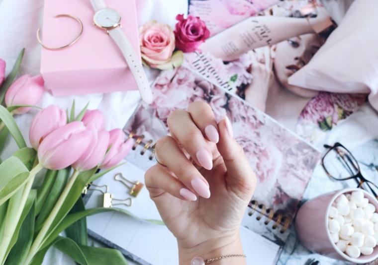 Smalto rosa antico, unghie forma stiletto, tulipani di colore rosa, mano di una donna