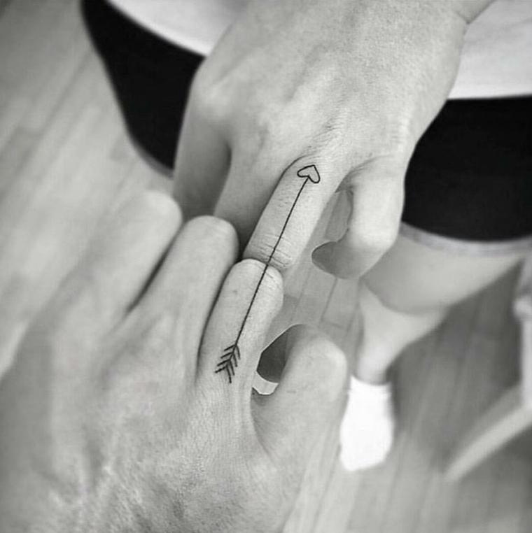 Tatuaggi di coppia, disegno cuore con freccia, tattoo diviso in due, tatuaggi sulle dita