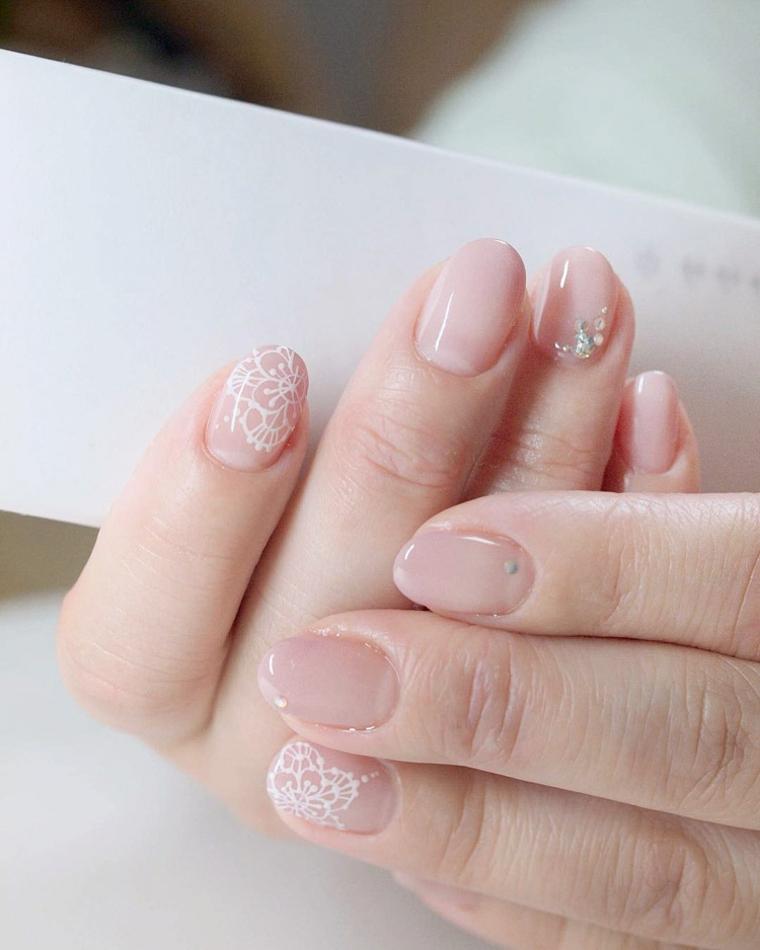 Unghie gel semplici, disegni pizzo colore bianco, accent nail brillantini, manicure corta forma arrotondata