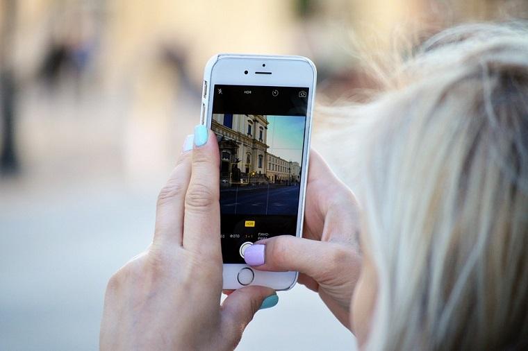 Come organizzare un viaggio, donna con telefono in mano, scattare una foto