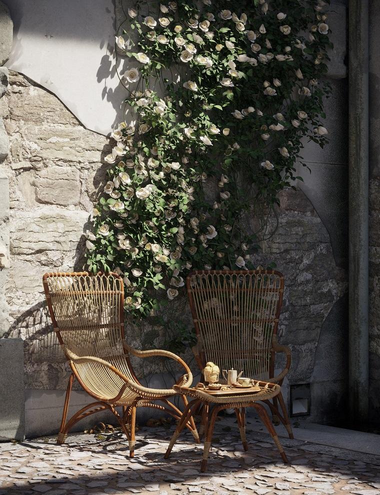 Giardino con mobili in legno, due sedie e tavolino, parete rustica con mattoni a vista