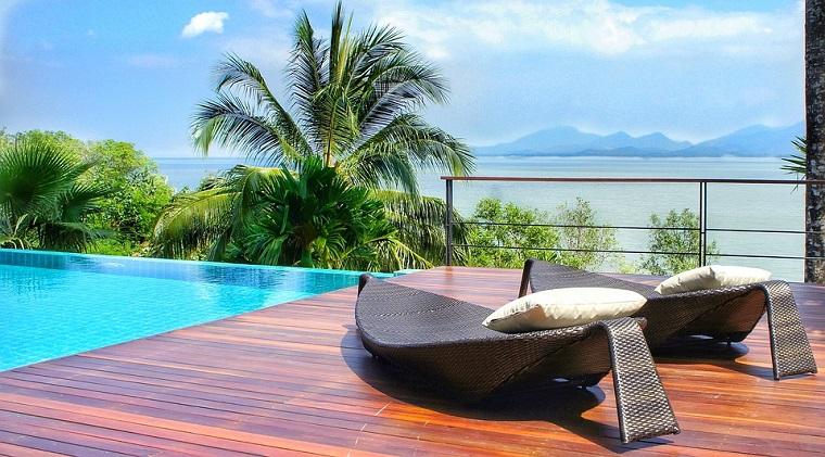 Casa con giardino, giardino con piscina, due sdrai in rattan, casa con vista mare