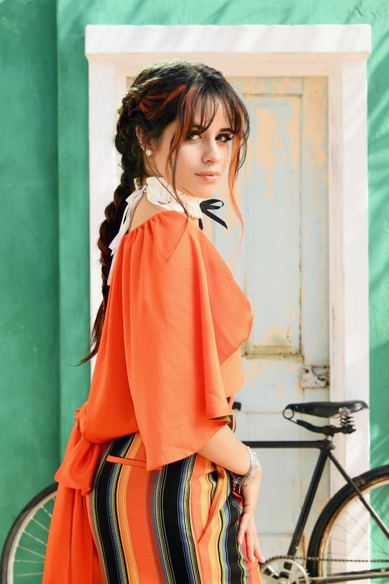 La cantante Camila Cabello, treccia capelli lunghi, acconciature bellissime, donna con bicicletta