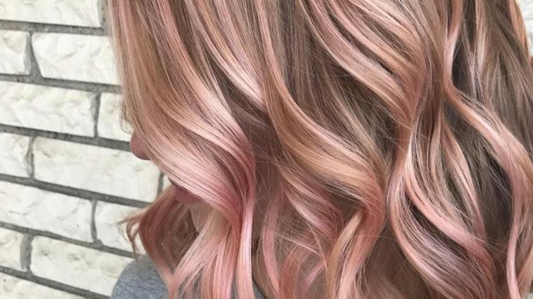 Pettinatura capelli onde, meches di colore rosa, shatush rosa, parete con mattoni