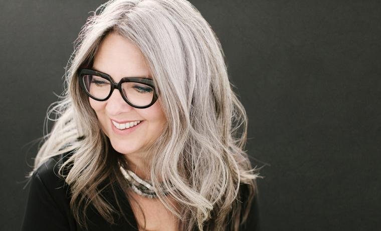 Capelli grigi corti, donna con riga centrale, occhiali da vista neri, donna con viso sorridente