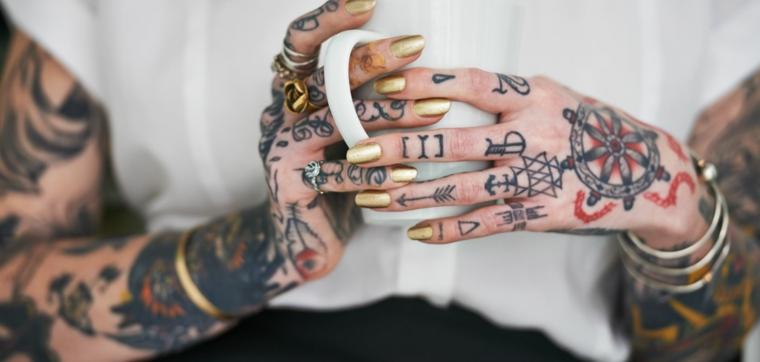 Donna con le braccia tatuate, tazza di porcellana tra le mani, tattoo numeri romani