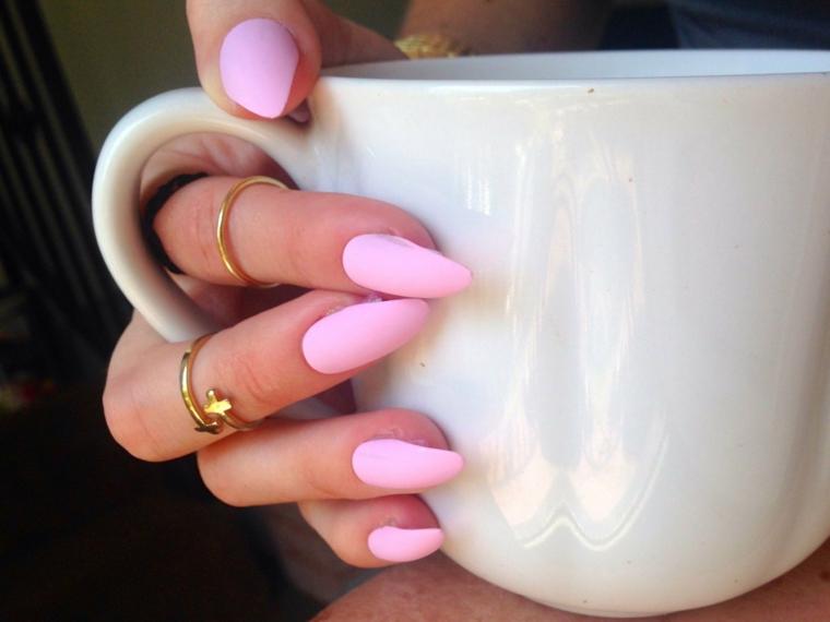 Smalto rosa opaco, anelli in oro, tazza bianca di porcellana, unghie rosa antico