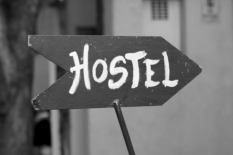 Freccia di legno con scritta, come organizzare un viaggio, tabella con scritta Hostel
