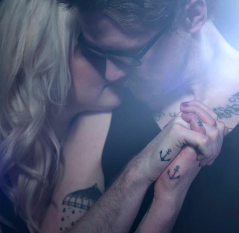 Uomo e donna abbracciati, tattoo ancora, tattoo fidanzati, uomo con tatuaggi