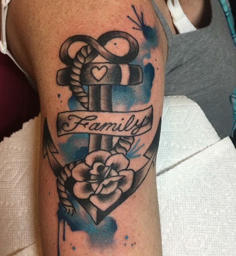 Donna con braccio tatuato, disegno tattoo ancora, scritta tatuaggio e fiore