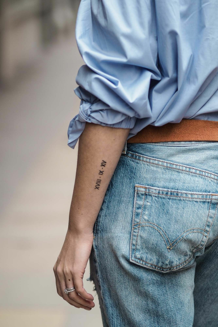 Tattoo numeri romani, donna con tattoo sul braccio, abbigliamento jeans e camicia