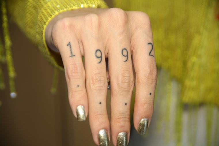 Tattoo anno 1992, tatto con punti sulle dita, tattoo stilizzati, donna con giacca gialla