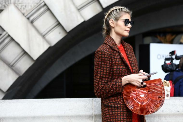 Donna con capelli biondo balayage, due trecce alla francese, borsa cesto rossa