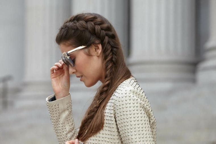 Capelli di colore castano, treccia laterale legata, donna con occhiali da sole, giacca di pelle bianca