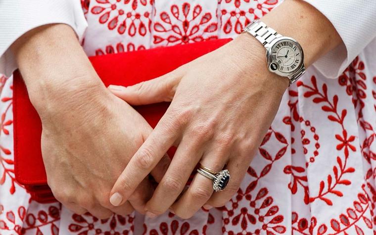 Borsetta clutch rossa, smalto colore rosa, unghie rosa cipria, orologio da polso donna