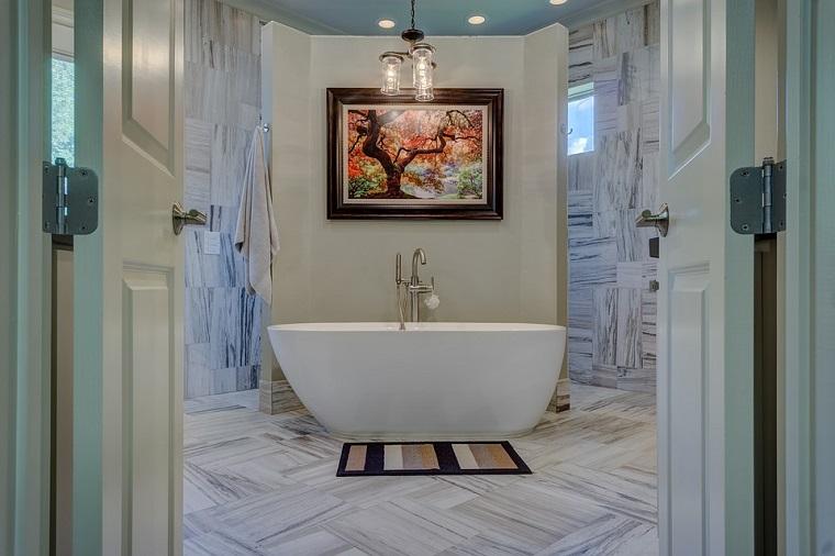 Vasca da bagno freestanding, rivestimento pareti piastrelle effetto legno, quadro appeso alla parete
