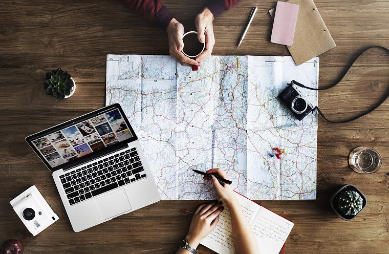 Vacanze fai da te, mappa con itinerario, laptop con foto, tavolo di legno