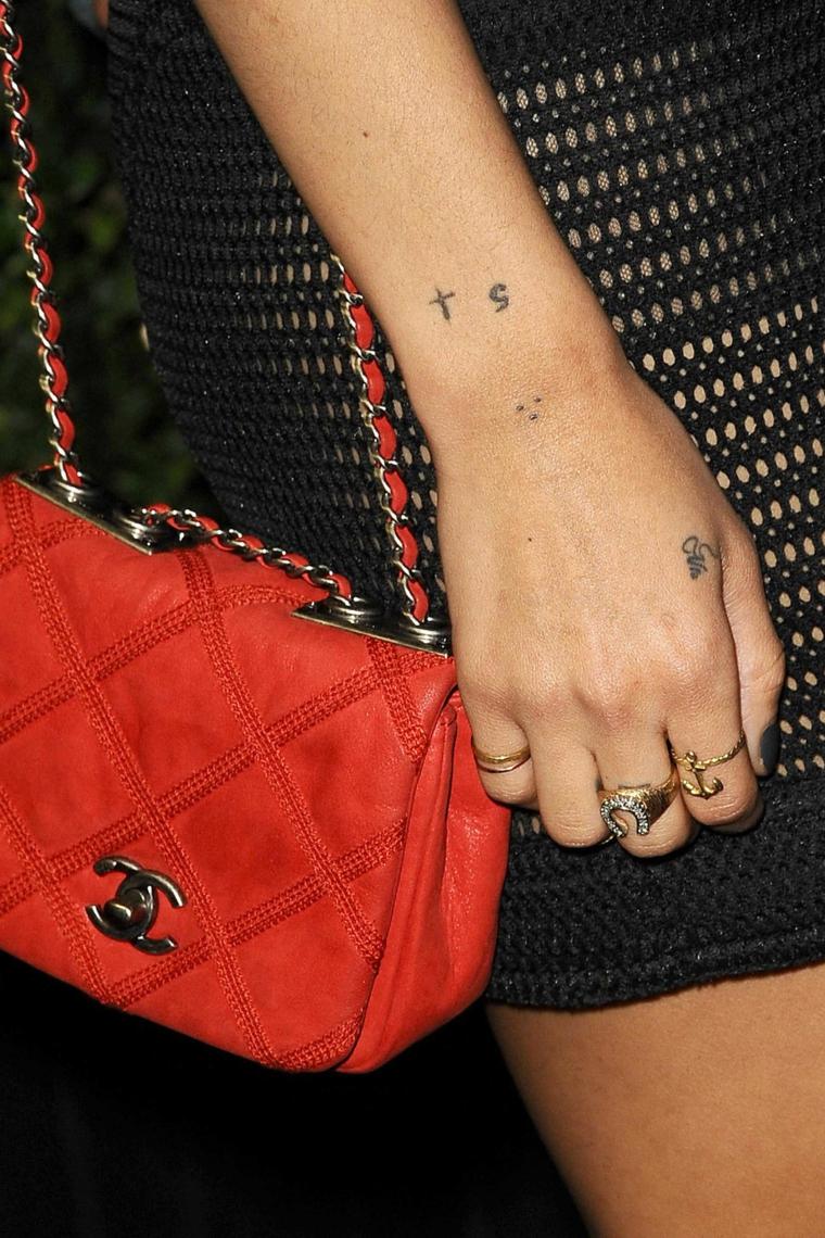Tatuaggi numeri, tattoo numero 5, anelli in oro con simboli, borsetta rossa tracolla