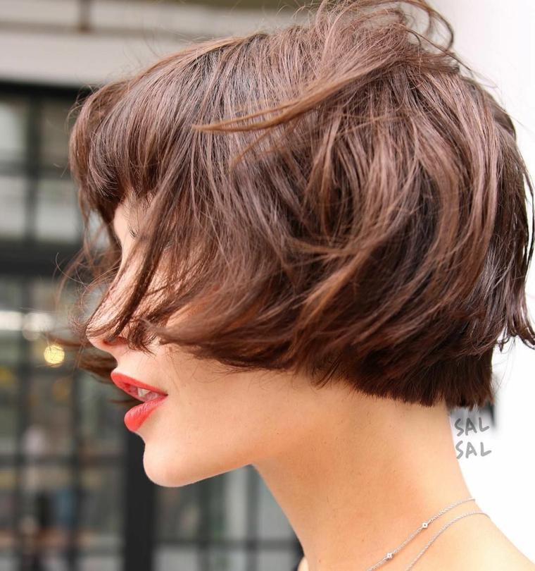 Taglio corto scalato, capelli di colore castano, acconciatura con frangia, donna con rossetto rosso