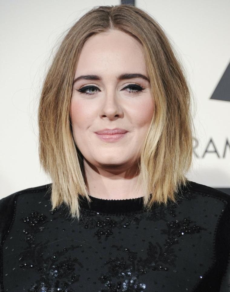 Donna con capelli biondi, acconciatura capelli long bob, la cantante Adele, abito nero con lustrini