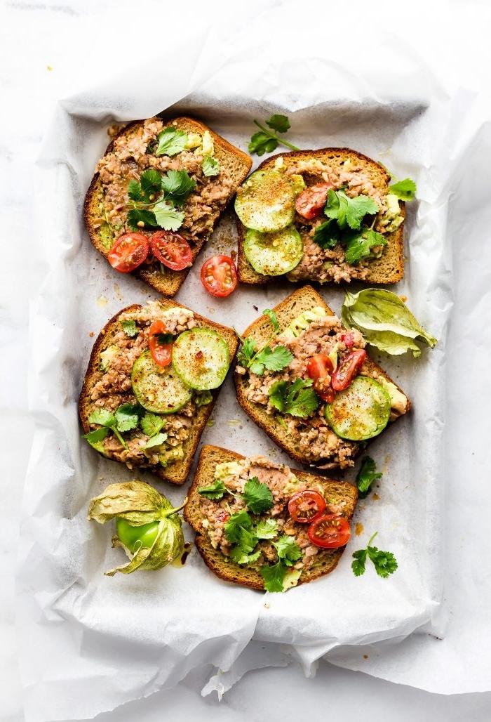 Ricette antipasti sfiziosi, fette di pane con verdure, teglia con carta da forno, bruschette con verdure