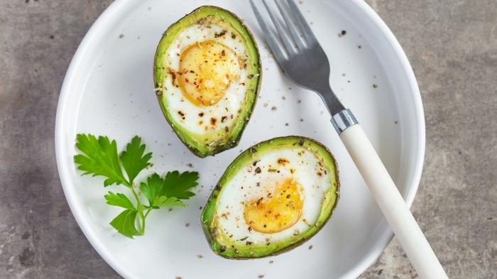 Idee brunch, avocado con ripieno di uova, uovo in camicia con prezzemolo