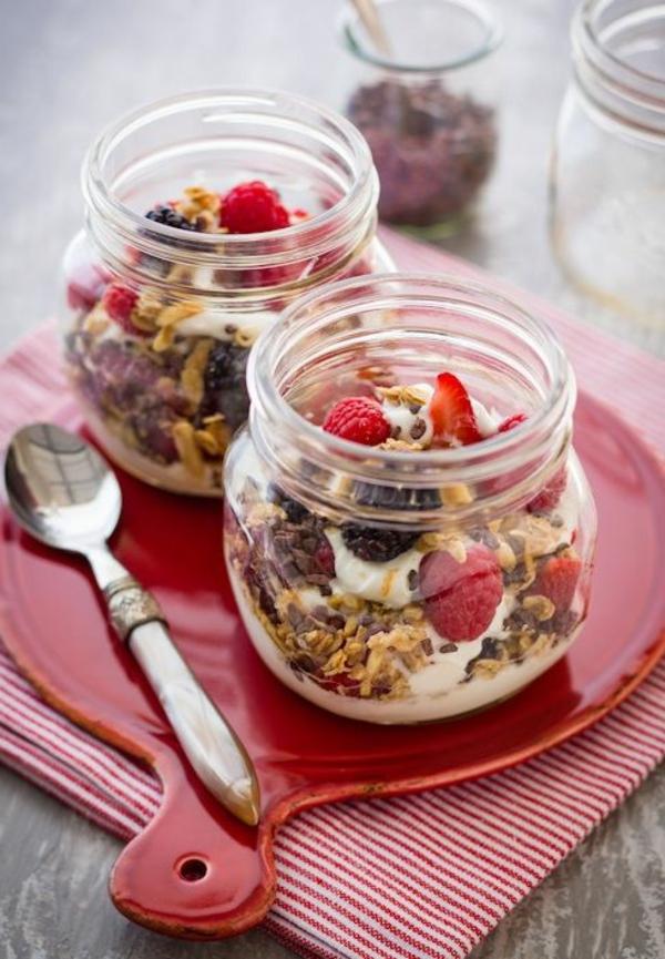 Colazione con yogurt e frutti di bosco, barattolo di vetro e cereali, fragole tagliate a fette