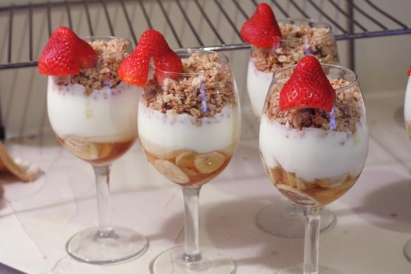 Bicchieri con dolce al cucchiaio, fette di banana sciroppata, fragole tagliate a fette