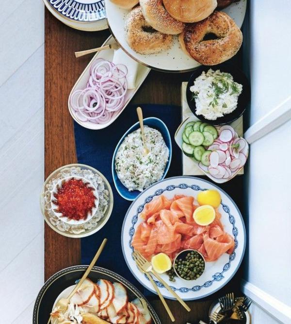 Piatto con salmone affumicato, ciotole con verdure, pannini rotondi, buffet per il brunch
