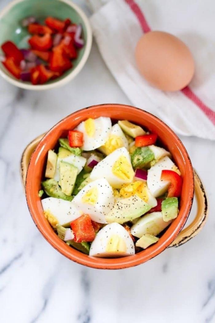 Piatto con uova sode, brunch con avocado e peperoni, ciotola con pezzettini di peperoni rossi