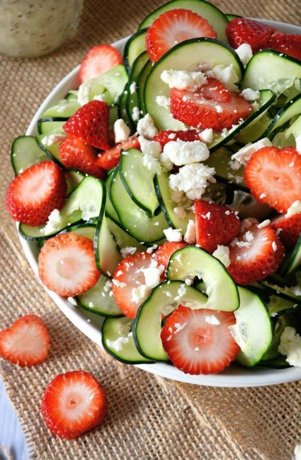 Piatto con verdure e frutta, fette di cetriolo e fragole, fragole con formaggio Feta